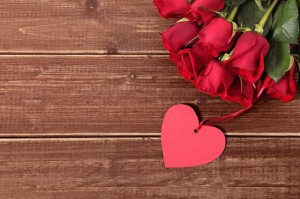 Valentine background of gift tag and red roses on wood. Space fo
